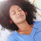Woman laying down and listening to audio